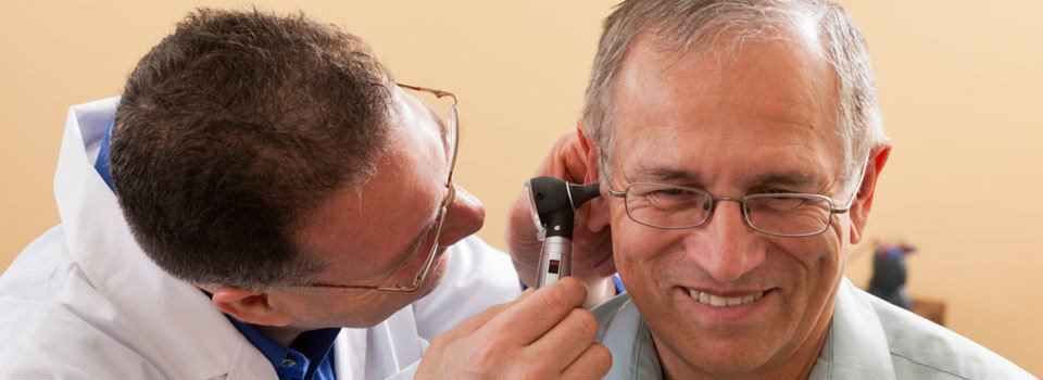 Audiologist examining a patient's ear